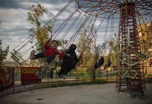 Mulheres e crianças se divertem em um parque de diversões recém reaberto em Raqqa, na Síria. A antiga capital do Estado Islâmico tenta renascer após ficar em ruínas por conta das batalhas para expulsar o grupo terrorista Foto: Yan Boechat