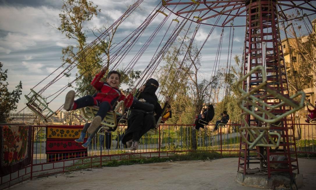 Mulheres e crianças se divertem em um parque de diversões recentemente reaberto em Raqqa. Muitos moradores da cidade síria ainda temem a volta do grupo Foto: Yan Boechat