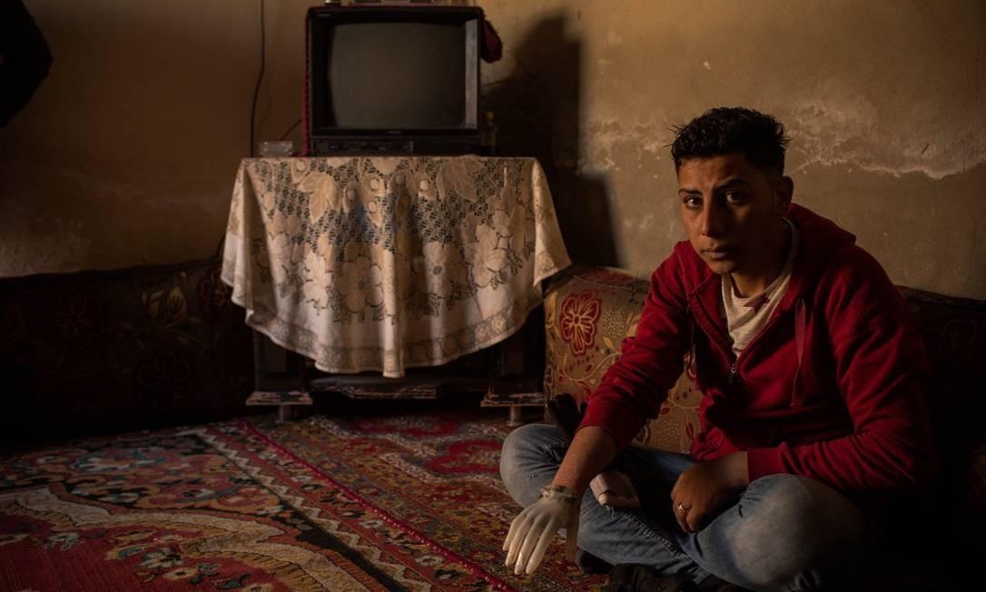 Abed Shebab, de 19 anos, teve a mão decepada por integrantes do Estado Islâmico ao ser acusado de furtar peças de motocicletas em Raqqa. Hoje ele usa uma mão de plástico de um manequim que ele encontrou sob os escombros de uma loja de roupas no centro de Raqqa Foto: Yan Boechat