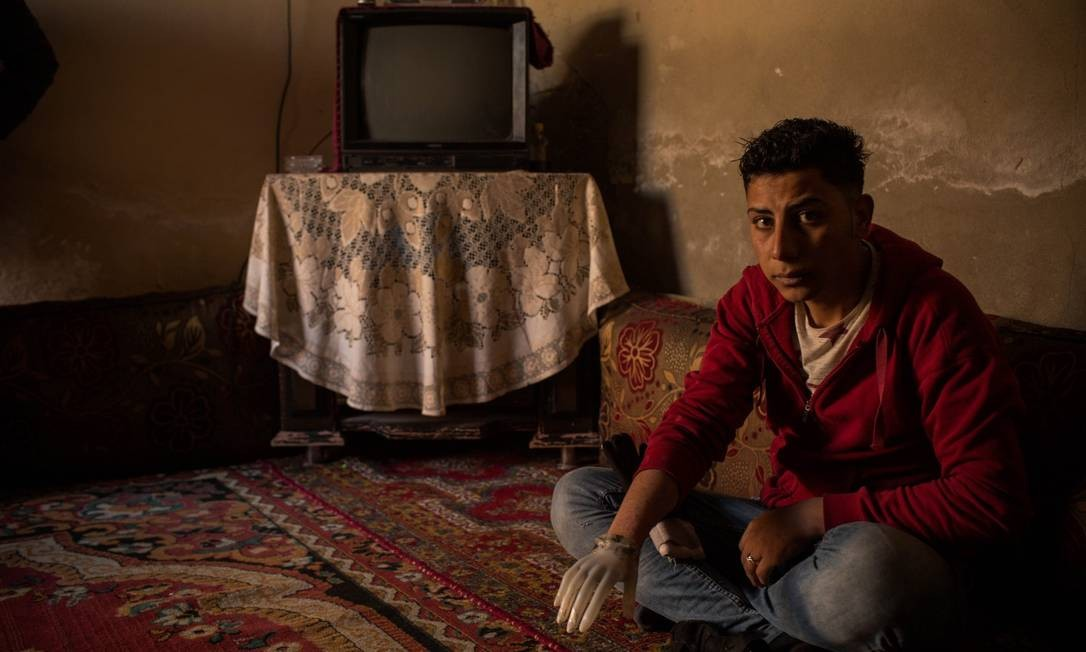 Abed Shebab, de 19 anos, teve a mão decepada por integrantes do Estado Islâmico ao ser acusado de furtar peças de motocicletas em Raqqa. Hoje ele usa uma mão de plástico de um manequim que ele encontrou sob os escombros de uma loja de roupas no centro de Raqqa Yan Boechat