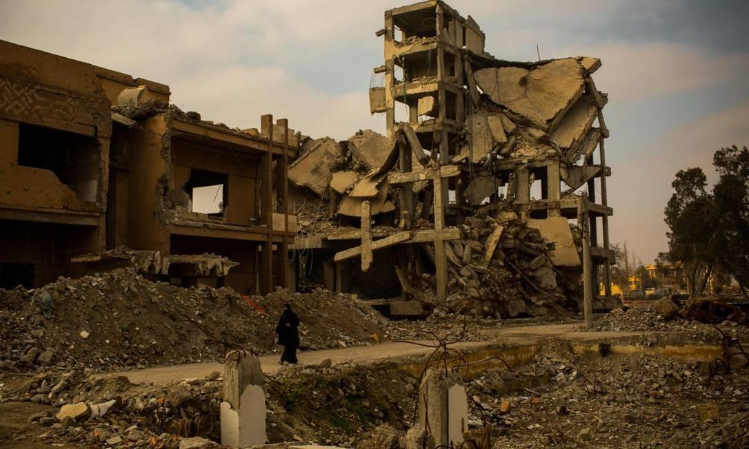 Mulher passa por prédios destruídos em Raqqa. Aos poucos, serviços básicos estão sendo retomados Foto: Yan Boechat