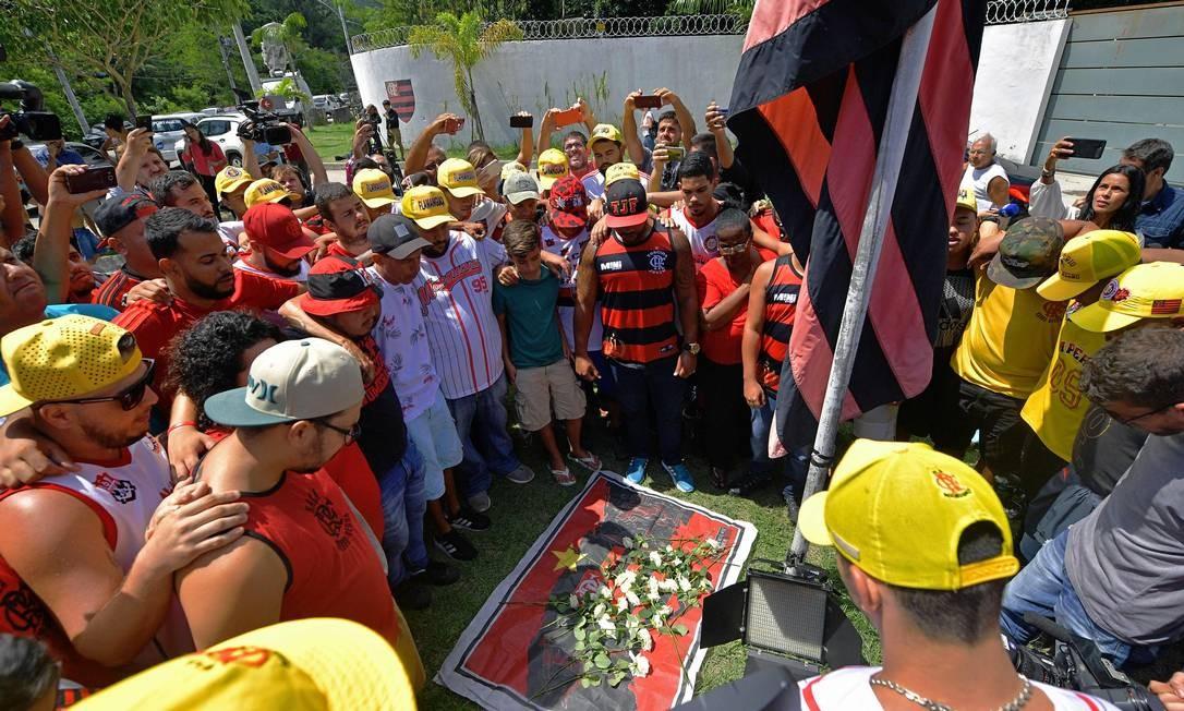 Torcedores do Flamengo se reúnem para colocar flores na entrada do Ninho do Urubu após o incêndio Foto: CARL DE SOUZA / AFP