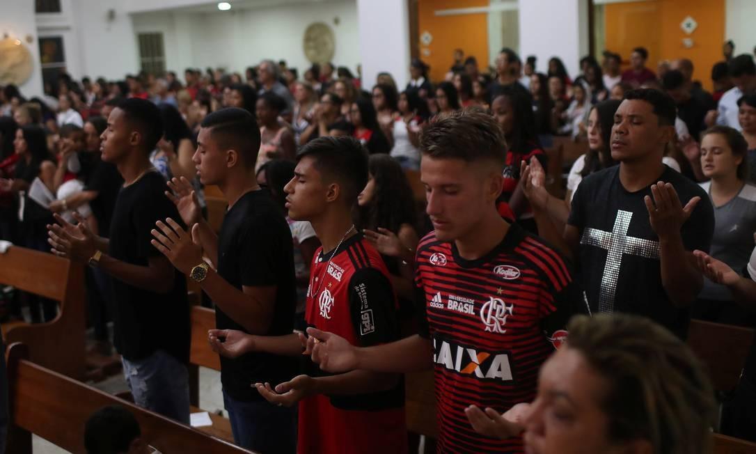 Torcedores do Flamengo rezam durante uma missa em memória das vítimas, em Vargem Grande, próximo ao Centro de Treinamento do Flamengo Foto: RICARDO MORAES / REUTERS