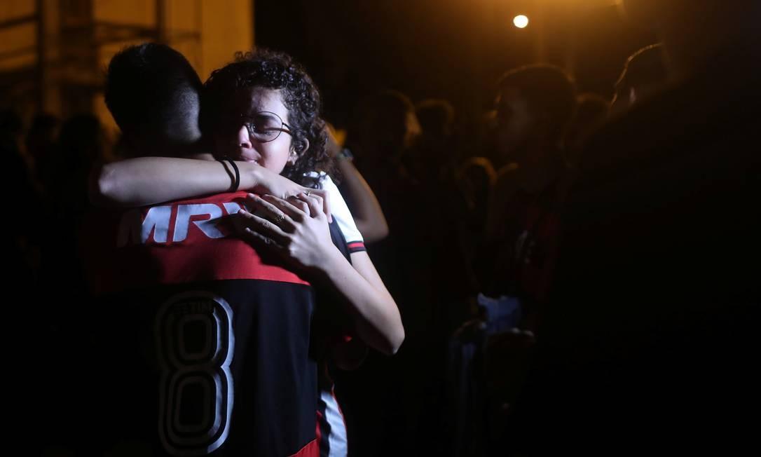 Leoni Pereira, jogador de futebol juvenil do Flamengo, é abraçado por torcedora após missa Foto: RICARDO MORAES / REUTERS