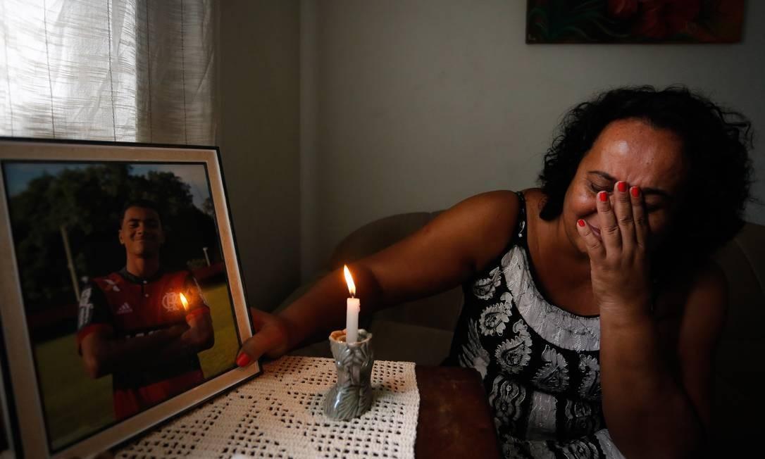 Marilia Barros da Silva mãe do Arthur Vinicius de Barros chora ao lado do retrato do filho Pablo Jacob / Agência O Globo
