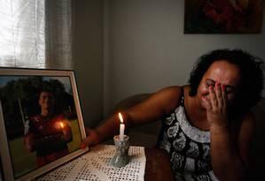 Marilia Barros da Silva mãe do Arthur Vinicius de Barros chora ao lado do retrato do filho Foto: Pablo Jacob / Agência O Globo