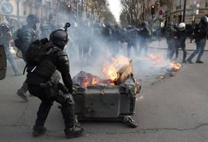 Policial retira barreira formada por lixeira em chamas durante protesto dos coletes amarelos em Paris Foto: ZAKARIA ABDELKAFI / AFP