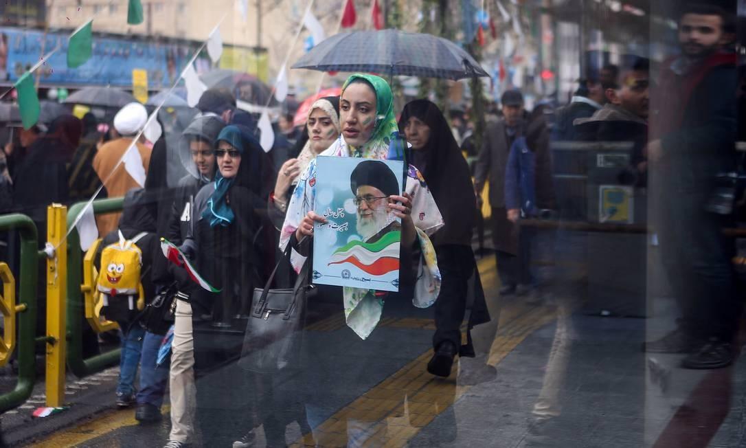 Uma iraniana carrega uma foto do líder supremo do Irã, o aiatolá Ali Khamenei, durante uma cerimônia para marcar o 40º aniversário da Revolução Islâmica em Teerã, Irã MASOUD SHAHRESTANI / TASNIM NEWS AGENCY / REUTERS