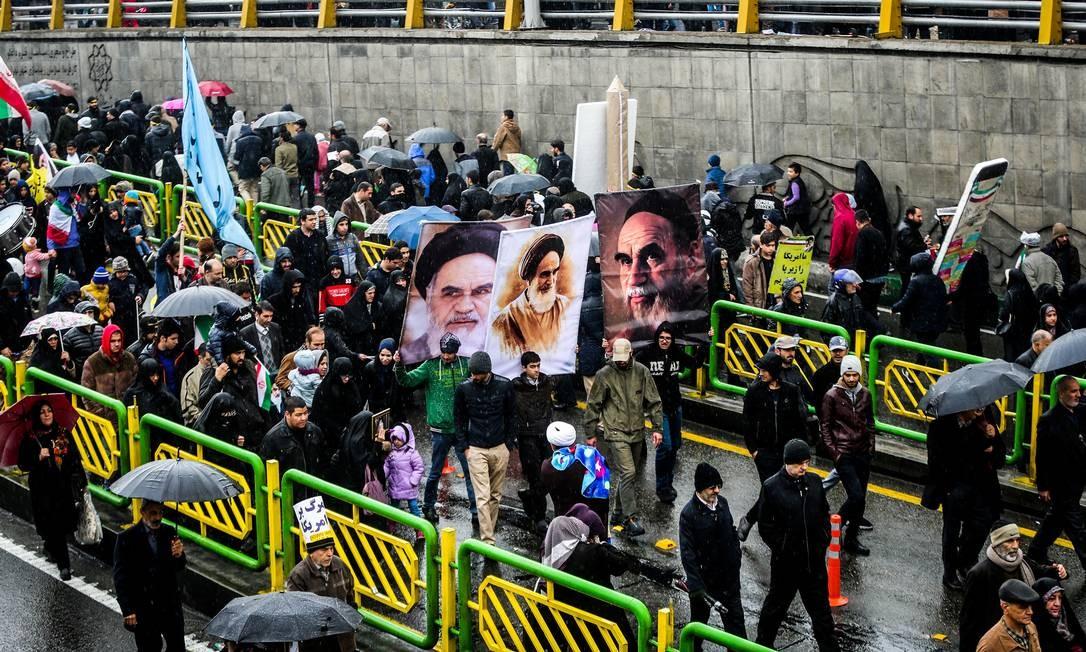 Carregando cartazes com fotos dos líderes do páis, iranianos lotam as ruas para celebrar os 40 anos do movimento que derrubou o xá Mohammad Reza Pahlavi do poder, em 1979 | VAHID AHMADI / TASNIM NEWS AGENCY / REUTERS