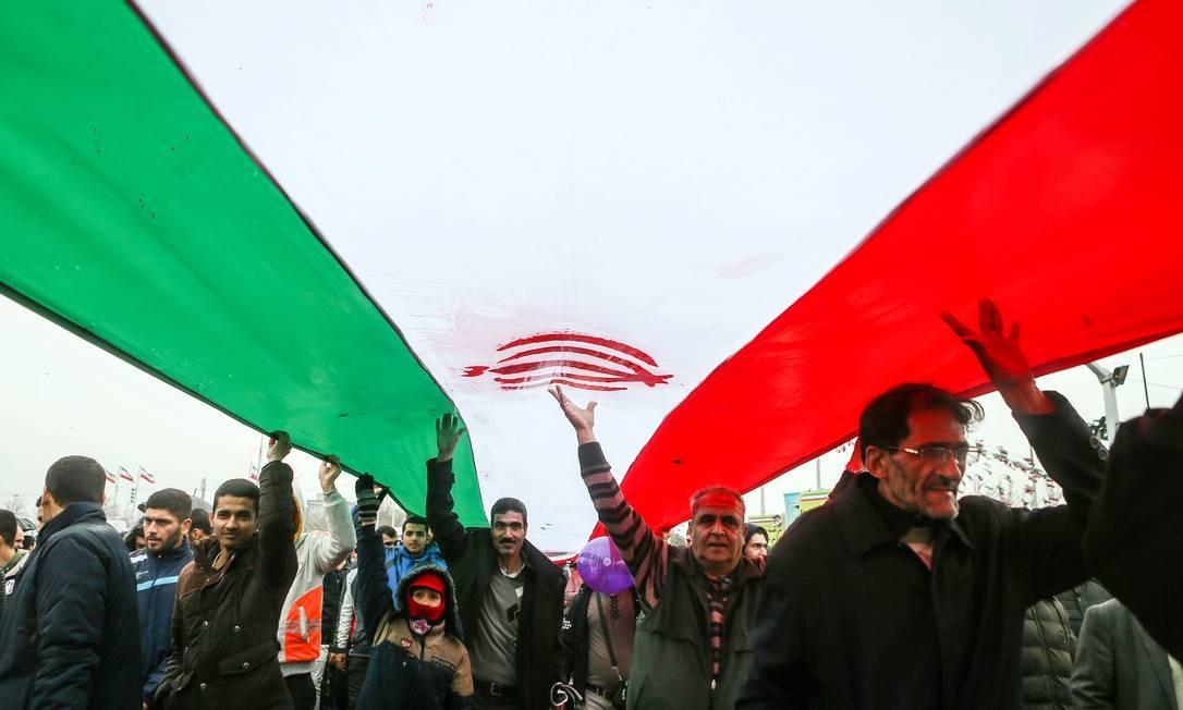 Iranianos marcham sob uma bandeira do Irã durante cerimônia que marca 40º aniversário da Revolução Islâmica | MASOUD SHAHRESTANI / TASNIM NEWS AGENCY / REUTERS