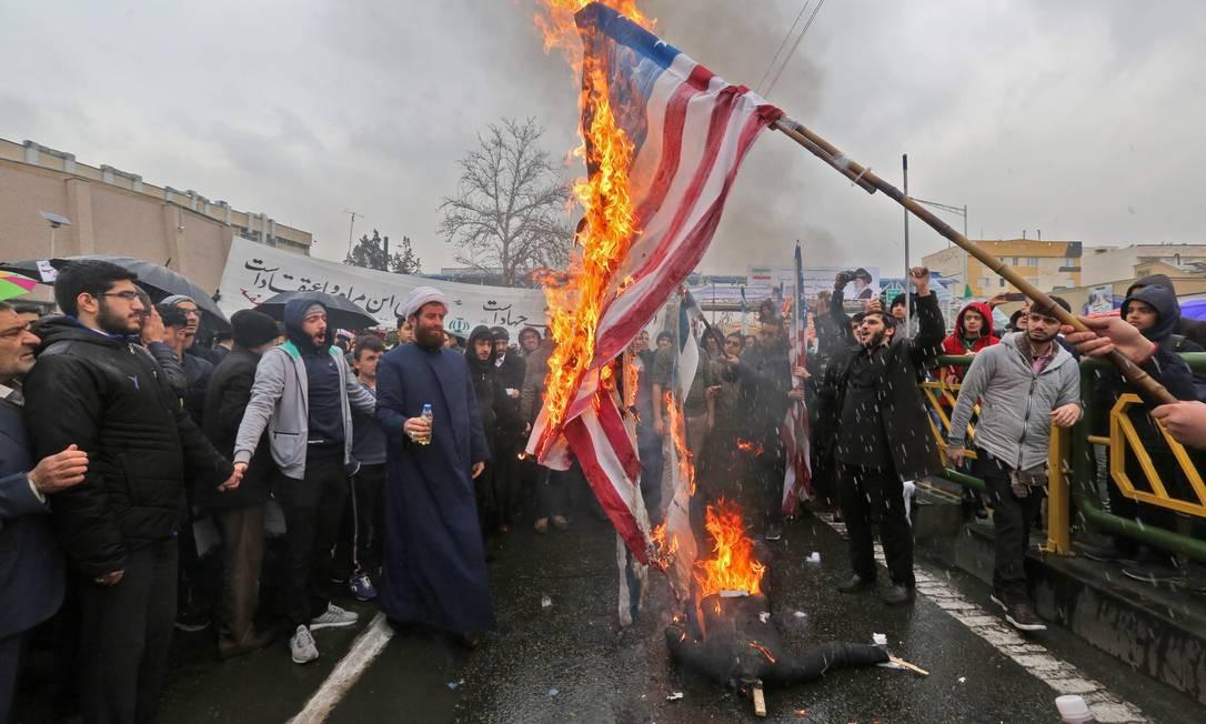 Iranianos queimam bandeiras dos Estados Unidos durante as comemorações do 40º aniversário da Revolução Islâmica na capital Teerã | Foto: ATTA KENARE / AFP