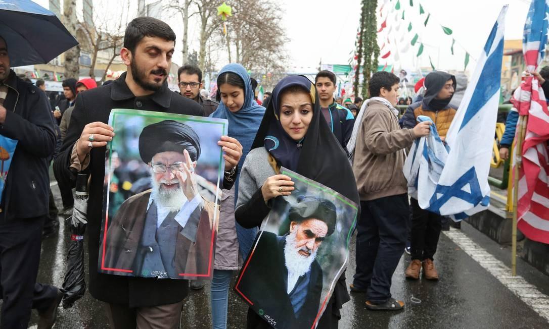 Um homem iraniano caminha com um retrato do líder supremo do país, Ali Khamenei, ao lado de uma mulher segurando outro fundador da Revolução Islâmica, aiatolá Ruhollah Khomeini | ATTA KENARE / AFP