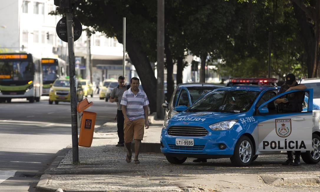 Pedestres caminham na Praia de Botafogo ao lado de viatura policial Foto: Márcia Foletto / Agência O Globo