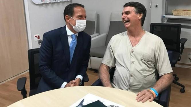 Doria, de máscara, visita o presidente Jair Bolsonaro no hospital e fala com ele sobre Previdência Foto: Divulgação