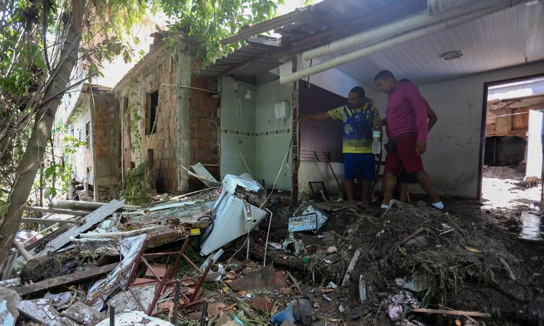 Moradores da localidade Jaqueira, no Vidigal, sobre montanha de lixo e destroços de casas destruídas pelo temporal Foto: Pedro Teixeira / Agência O Globo