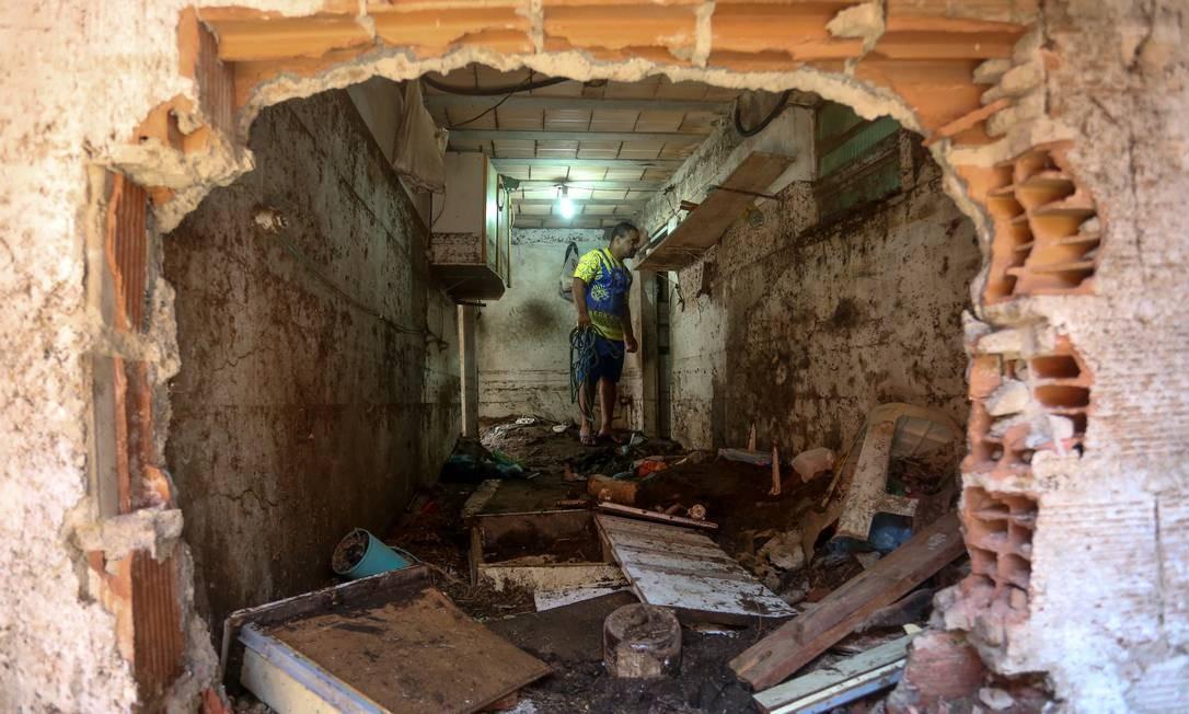 Morador anda pelos escombros do que restou da casa atingida por uma pedra durante o último temporal Foto: Pedro Teixeira / Agência O Globo