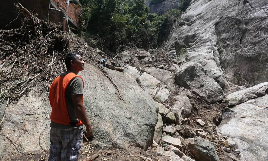 Morador observa ponto onde houve deslizamento de pedras e pode haver mais desmoronamentos na parte alta da comunidade do Vidigal Foto: Pedro Teixeira / Agência O Globo