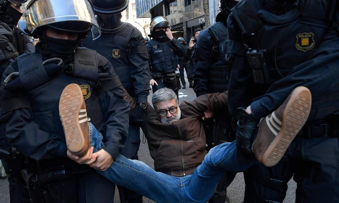 Forças policiais regionais da Catalunha carregam o parlamentar catalão Carles Riera, da Candidatura Popular, depois que ele se juntou a manifestantes que bloqueavam uma rua em Barcelona para protestar contra o julgamento de líderes separatistas catalães, nesta terça. Doze separatistas estão sendo julgados pelo Tribunal Supremo, em Madri, por atuarem, em 2017, na tentativa fracassada de se separar da Espanha Foto: LLUIS GENE / AFP