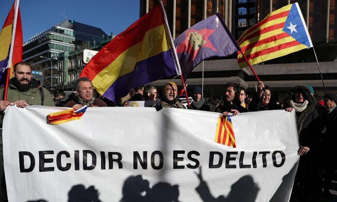 """Manifestantes exibem bandeiras catalãs e republicanas espanholas durante protesto em frente ao Tribunal Supremo, em Madri, e uma faixa em que se lê: """"Decidir não é crime"""", em referência ao referendo separatista considerado ilegal pelo governo central Foto: SUSANA VERA / REUTERS"""