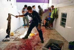 Morador recolhe uma roupa na casa em que dez pessoas foram mortas, no Morro do Fallet Foto: Pilar Olivares / Reuters