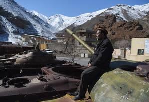 Homem afegão sentado nos restos de tanques da era soviética Foto: WAKIL KOHSAR / AFP