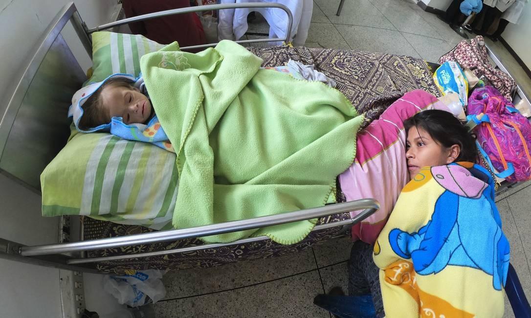 Mãe acompanha seu bebê desnutrido na cama de um hospital em Maracay, no estado de Aragua, na Venezuela. Drama de mães e crianças subnutridas é generalizado no país | Foto: YURI CORTEZ / AFP