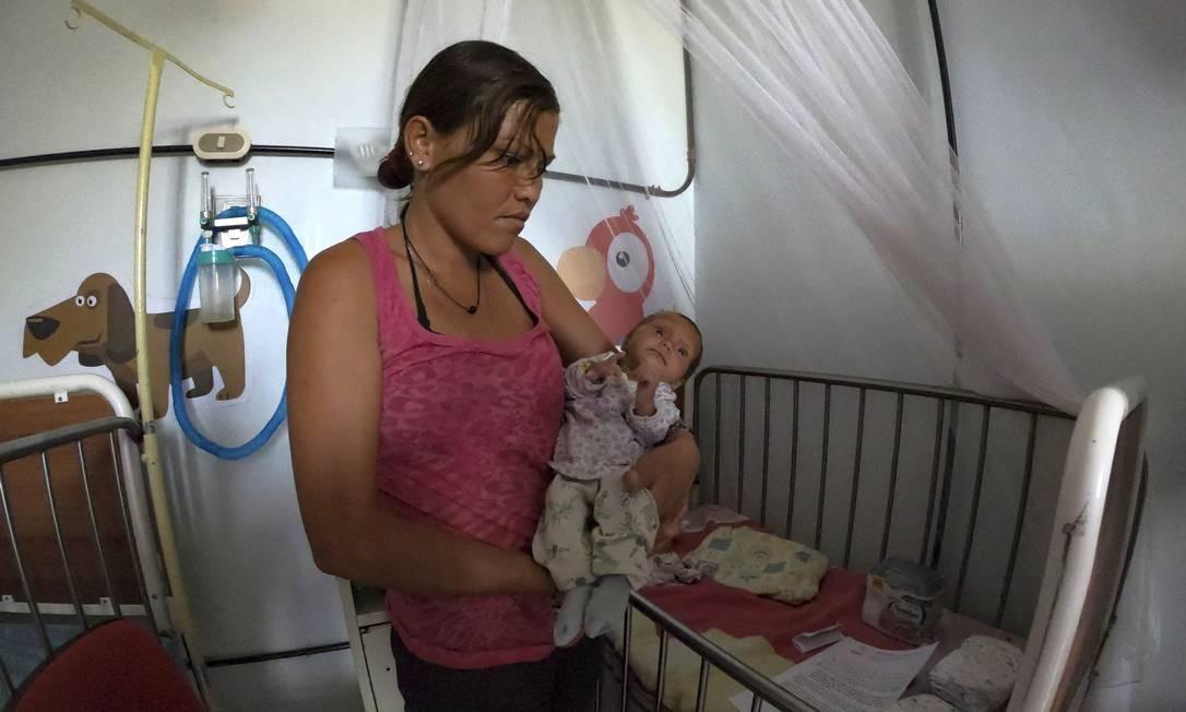 Outra mãe segura seu bebê subnutrido em um hospital em Maracay. Toneladas de medicamentos, alimentos e itens básicos estão estocados em Cúcuta, na Colômbia, à esperar de atravessar a fronteira Foto: YURI CORTEZ / AFP