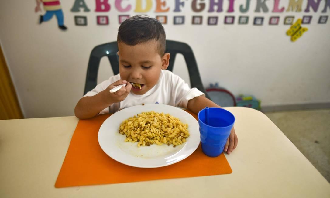 O pequeno Jaiser Rodríguez, 5 anos, come no abrigo da Fundação Kapuy – onde recebeu tratamento para desnutrição Foto: YURI CORTEZ / AFP