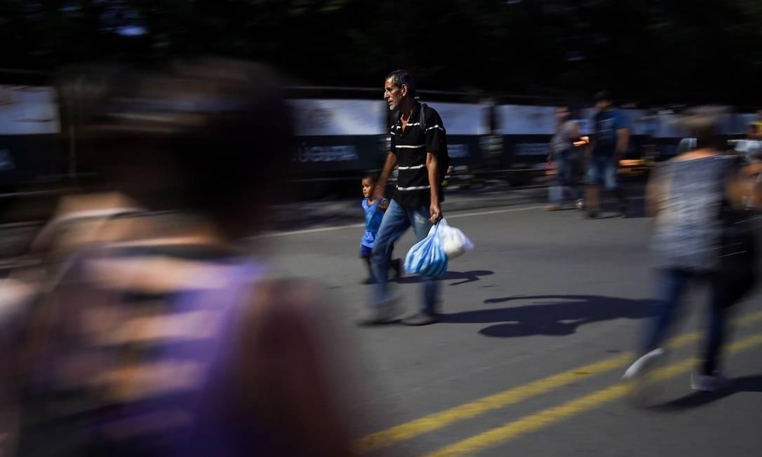 Pessoas atravessam a Ponte Internacional Francisco de Paula Santander, que liga as cidades de Cúcuta, na Colômbia, e Ureña, na Venezuela. Toneladas de medicamentos, alimentos e itens básicos enviados pelo governo americano estão estocadas na cidade, à espera da liberação da fronteira pelos militares venezuelanos Foto: LUIS ROBAYO / AFP