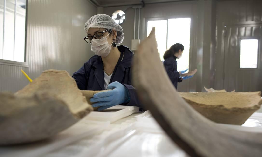 No laboratório provisório montado em um contêiner na área externa do museu, uma funcionária trabalha na limpeza e na restauração de peças de cerâmica salvas Foto: Márcia Foletto / Agência O Globo