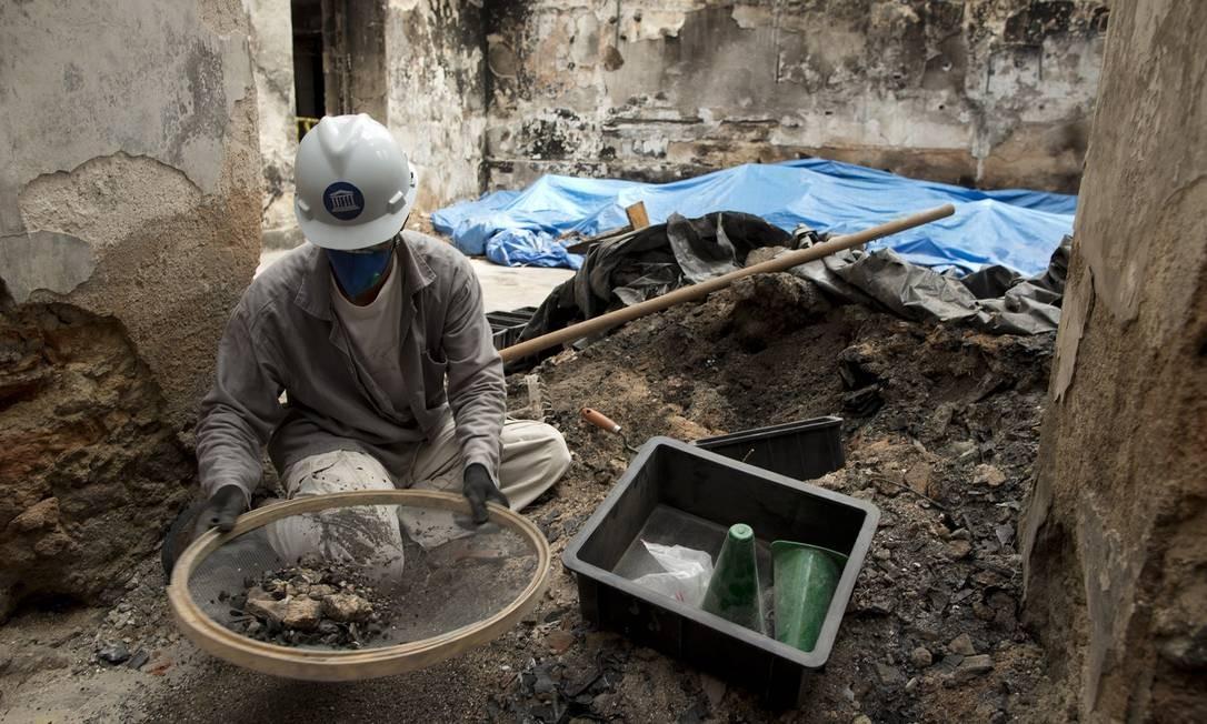 """Operário trabalha """"peneirando"""" escombros para tentar encontrar itens do acervo Foto: Márcia Foletto / Agência O Globo"""
