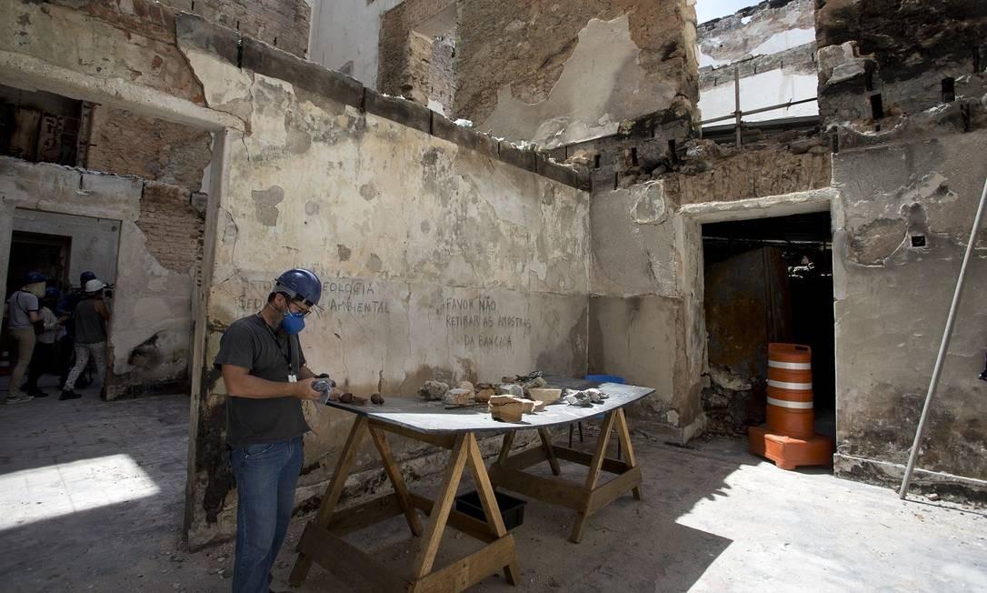 Fabiano Faulstich, curador da exposição de mineralogia do Museu Nacional, trabalha analisando amostras recuperadas, que estão sobre a bancada Foto: Márcia Foletto / Agência O Globo