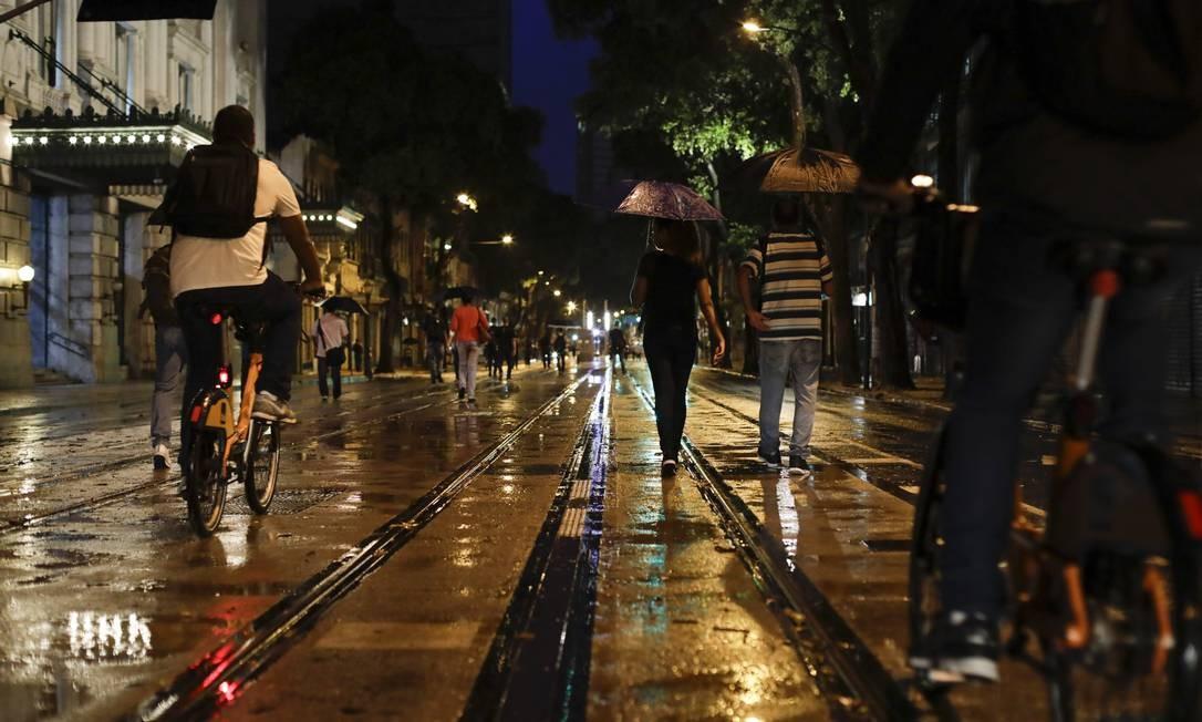 Já nas primeiras horas da manhã, trabalhadores enfrentavam a chuva para chegar ao trabalho na região da Central do Brasil| Foto: Gabriel Monteiro / Agência O Globo