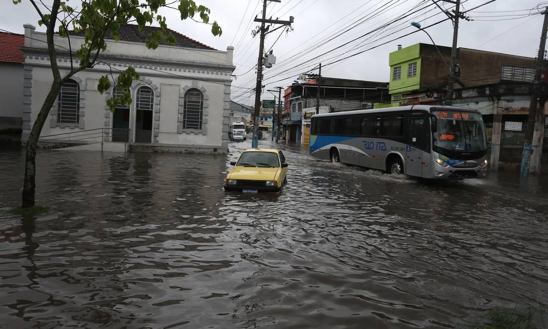 Um carro fica enguiçado na Rua Dr. Oliveira Botelho, em Neves, em frente à antiga 73ª DP. Água cobriu as rodas do veículo | Foto: Fabiano Rocha / Agência O Globo
