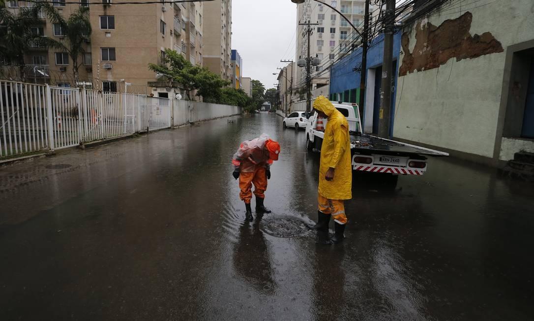Garis tentam desentupir bueiro na Rua General Bruce, em São Cristóvão | Foto: Pablo Jacob / Agência O Globo