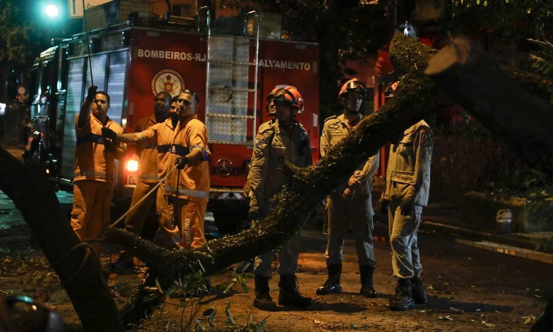 Funcionários da Comlurb e soldados dos Bombeiros retiram árvore caída em decorrência da chuva na Rua Constante Ramos, em Copacabana | Foto: Gabriel Monteiro / Agência O Globo