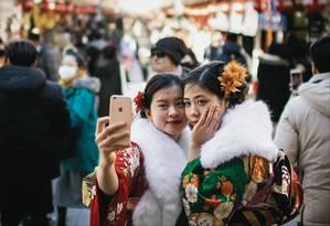 Duas mulheres vestidas com quimono posam para uma selfie nos arredores do templo Senso-ji, na região de Asakusa, em Tóquio Foto: MARTIN BUREAU / AFP