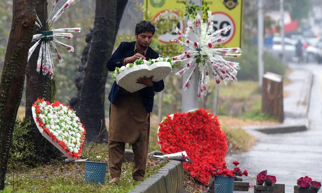 Um vendedor paquistanês prepara buquês de flores em forma de coração em uma estrada de Islamabad Foto: AAMIR QURESHI / AFP