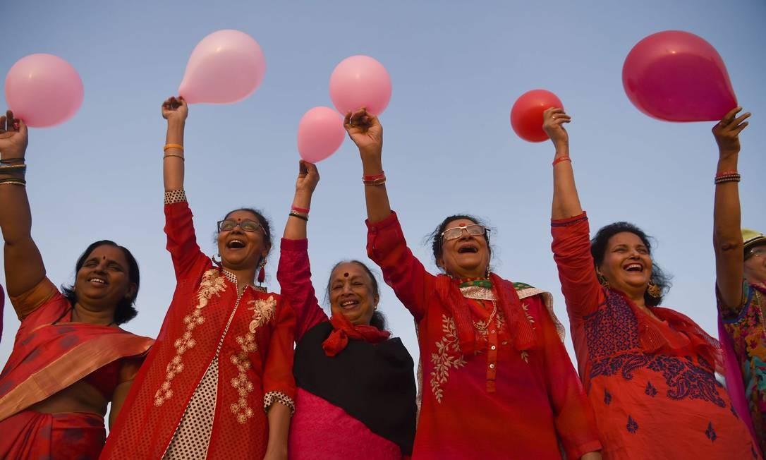 """Mulheres idosas indianas seguram balões durante ato para comemorar o """"Dia dos Namorados"""" na praia de Girgaon Chowpatty em Mumbai Foto: INDRANIL MUKHERJEE / AFP"""
