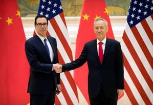 O secretário do Tesouro americano, Steven Mnuchin, e o vice-premiê chinês, Liu He, se cumprimentam antes da reunião para discutir política comercial. Foto: MARK SCHIEFELBEIN / AFP