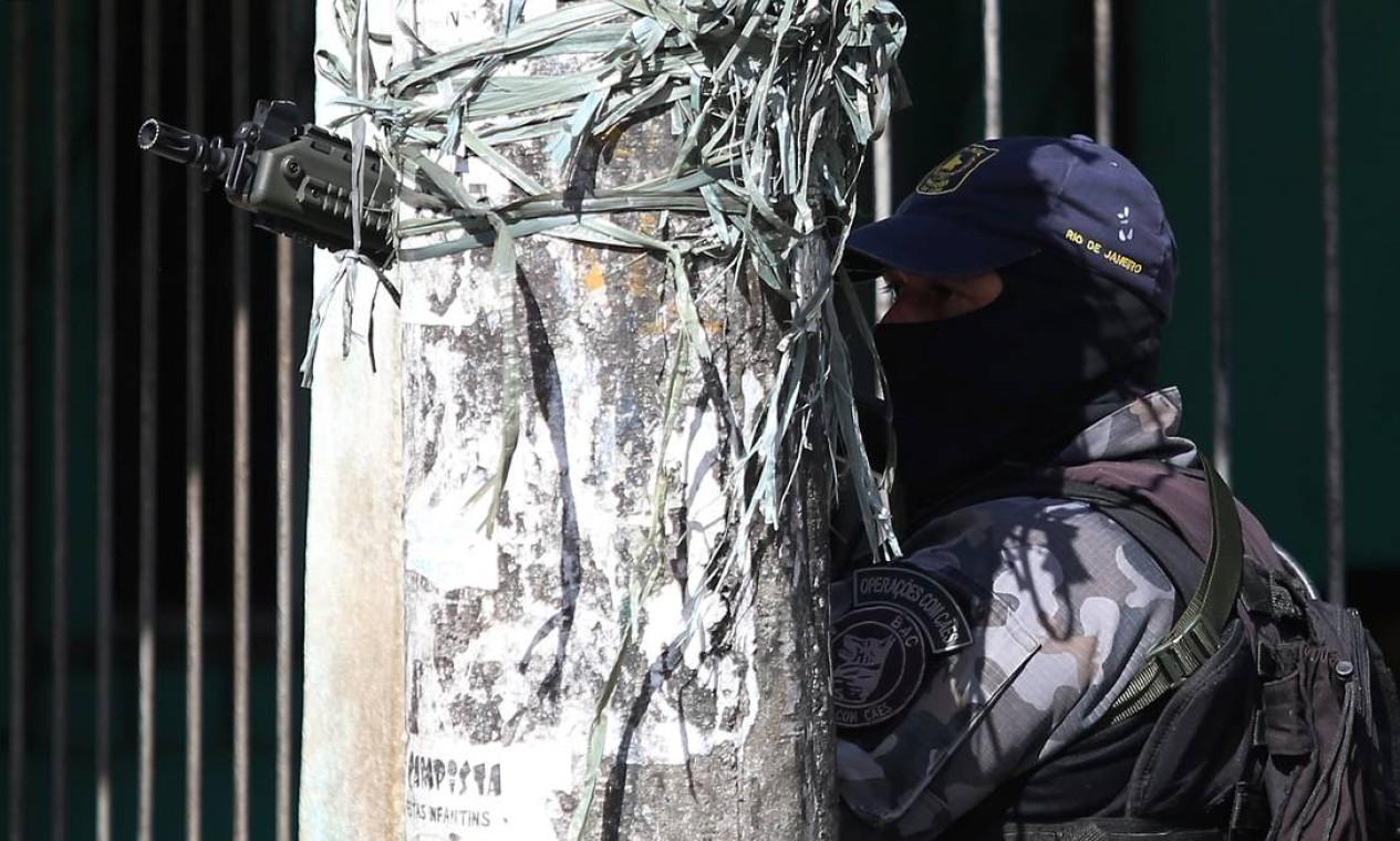 Policial se protege atrás de poste durante a operação Foto: Fabiano Rocha / Agência O Globo