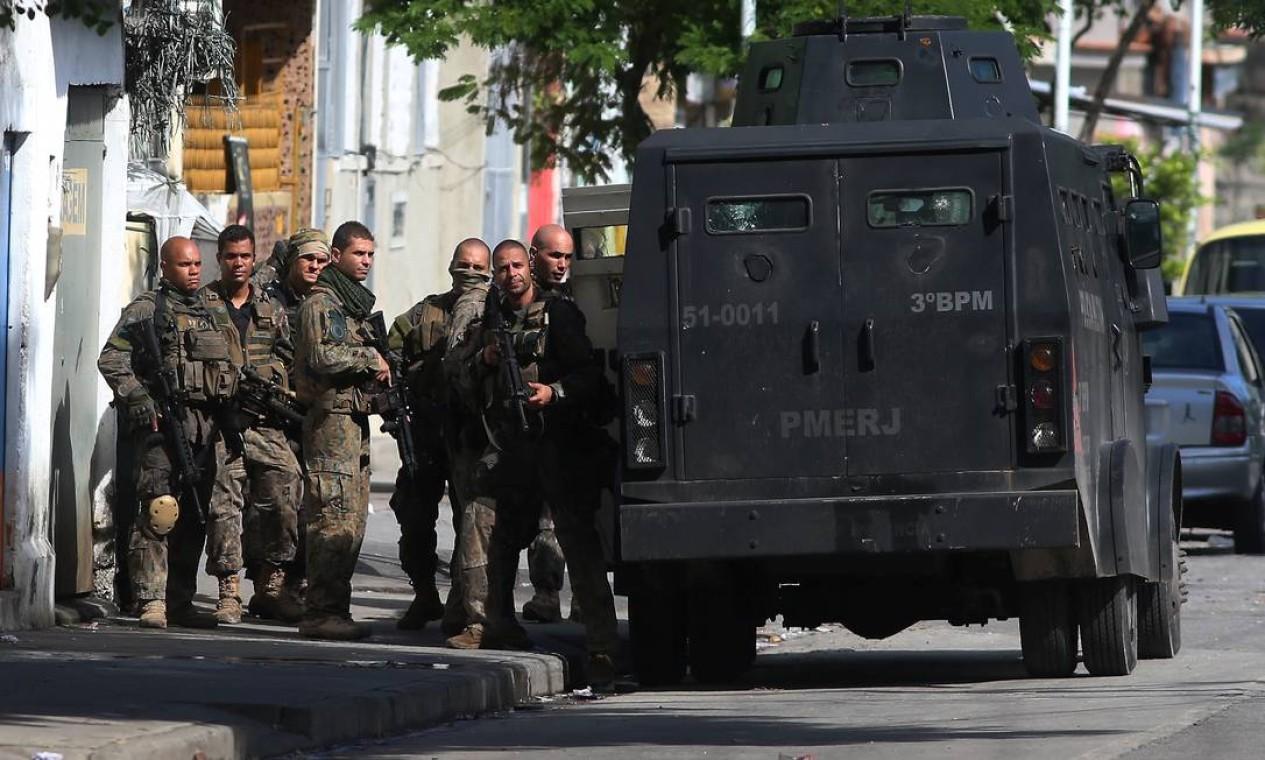 Policiais se preparam para entrar na comunidade com auxílio de um blindado Foto: Fabiano Rocha / Agência O Globo