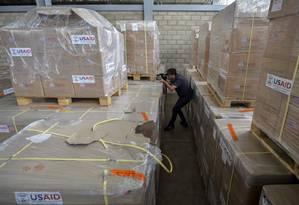 Homem fotografa ajuda americana para a Venezuela estocada em Cúcuta, na Colômbia Foto: LUIS ROBAYO / AFP