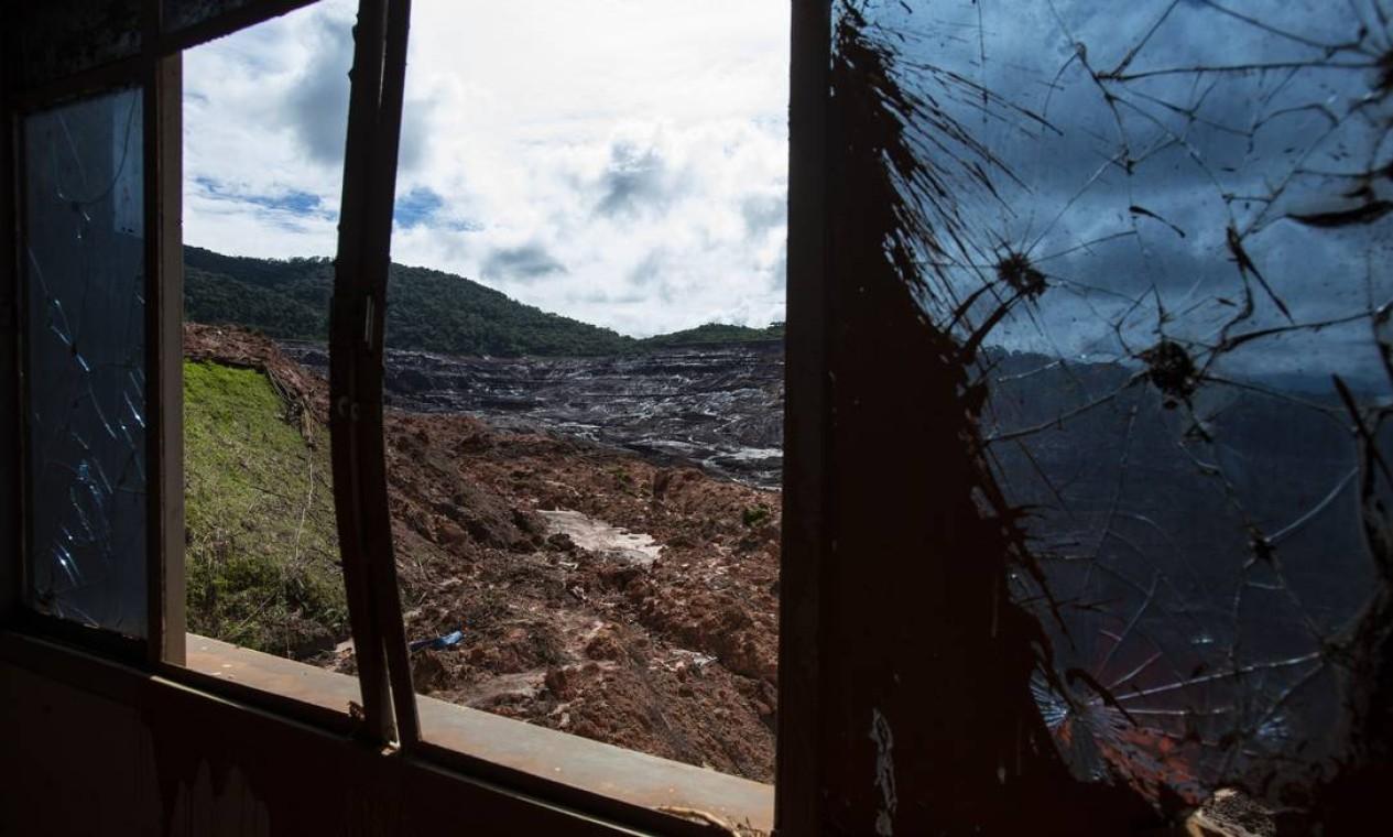 """Os vidros que restaram nas janelas estão trincados e parecem ter sido atingidos, assim como as paredes, por """"balas de canhão""""; consequência da tsunami de lama Foto: Alexandre Cassiano / Agência O Globo"""