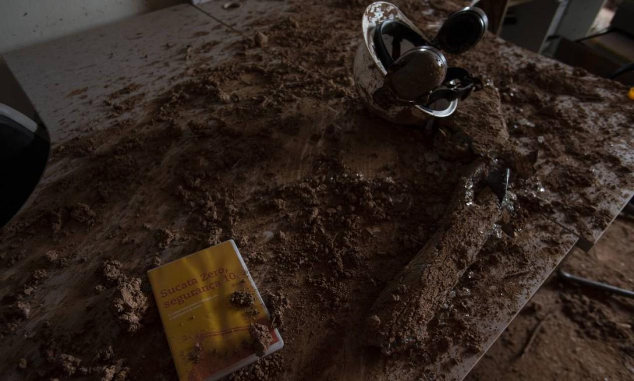 """Numa das mesas cheias de lama, um DVD intitulado """"Sucata zero, segurança 10"""" se sobressai junto com um capacete; equipamentos de segurança ficaram espalhados pelo local Foto: Alexandre Cassiano / Agência O Globo"""