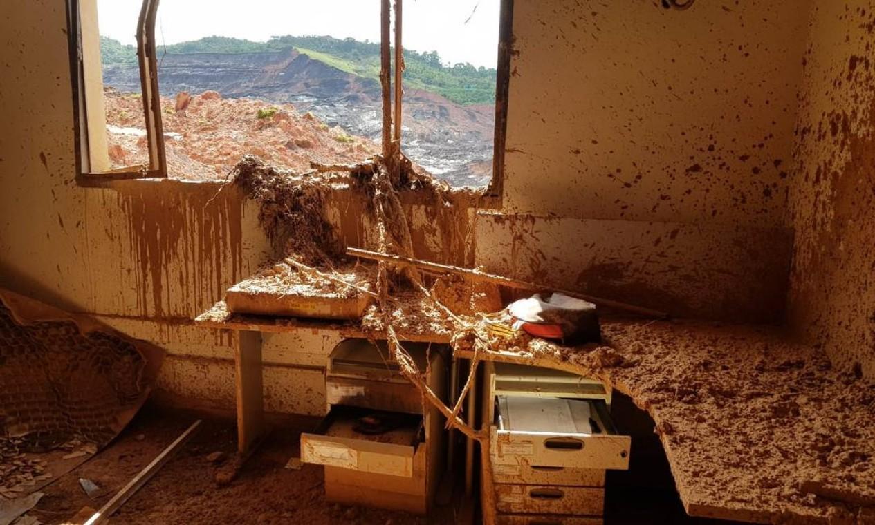Sem vidros e invadida pela lama e por galhos de árvores que foram arrastados por ela, a janela da ITM dá vista para a barragem da Vale Foto: Alexandre Cassiano / Agência O Globo