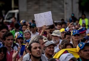 Manifestante segura placa que diz