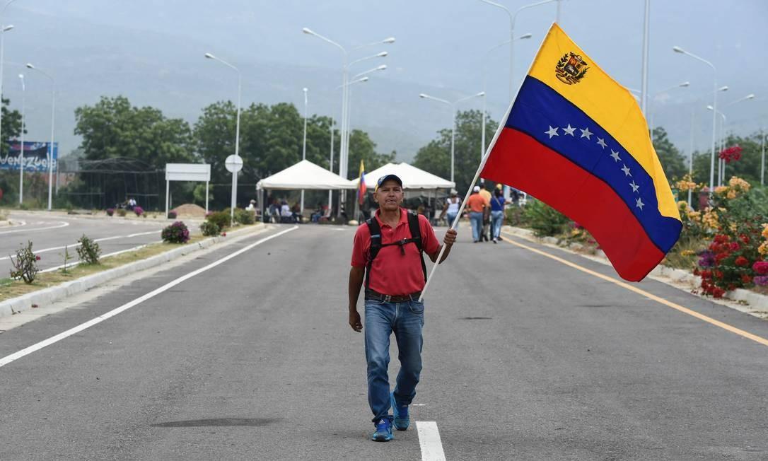 Um homem caminha empunhando uma bandeira venezuelana na ponte de Tienditas, que liga Ureña, na Venezuela, e Cúcuta, na Colômbia Foto: JUAN BARRETO / AFP
