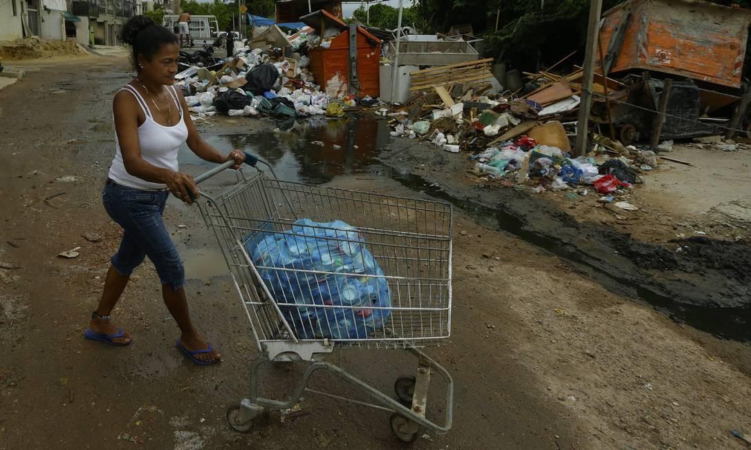 A cabeleireira Juling Rodríguez carrega latas para vender por peso em um depósito de recicláveis perto da Casa de Acolhimento da Caritas, no Recreio: R$ 3,50 por quilo Foto: / Antonio Scorza