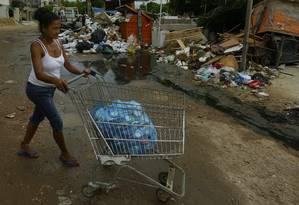 A cabeleireira Juling Rodríguez carrega latas para vender por peso em um depósito de recicláveis perto da Casa de Acolhimento da Caritas, no Recreio: R$ 3,50 por quilo Foto: Antonio Scorza